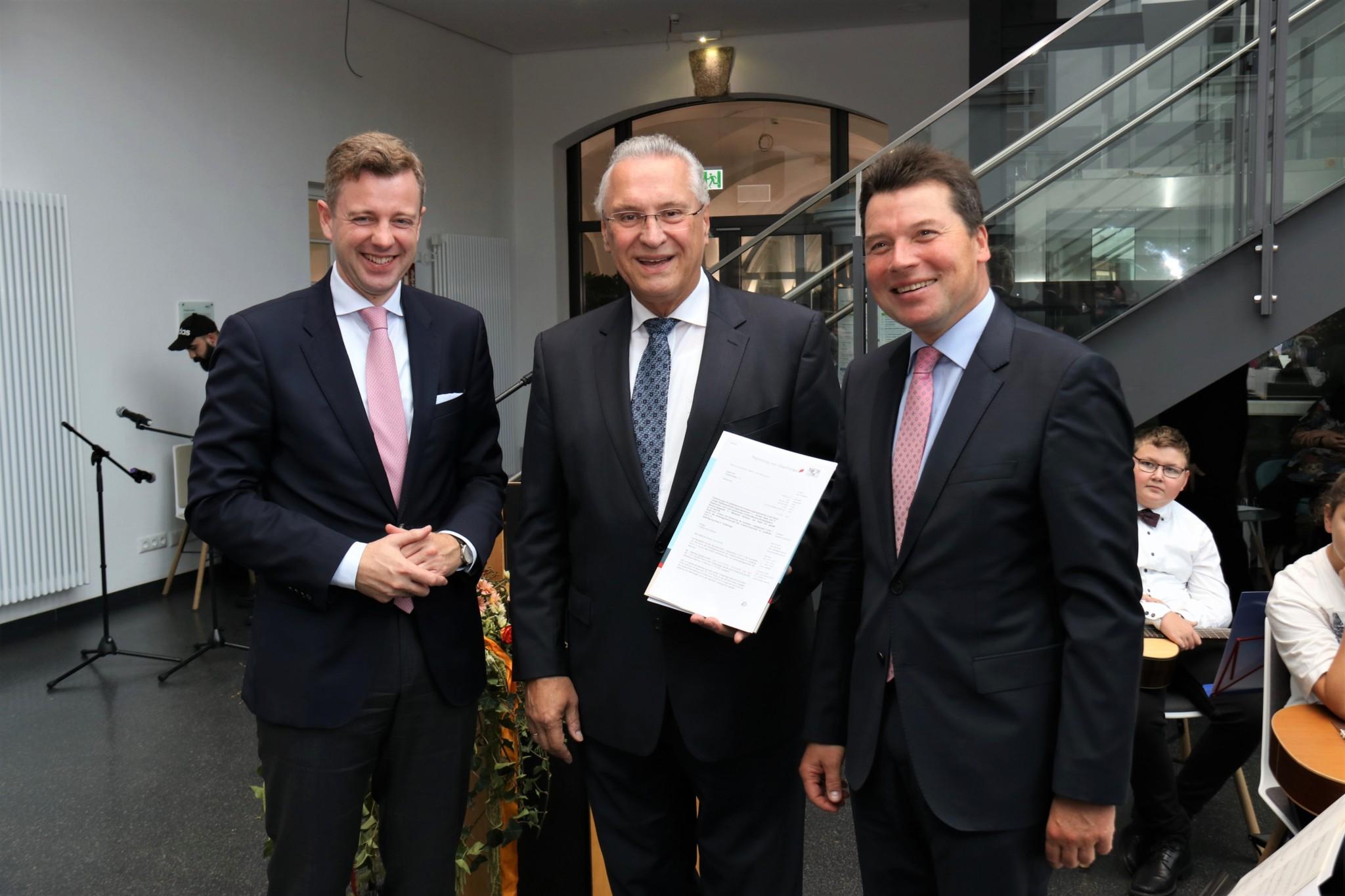 Bayerns Innenminister Joachim Herrmann übergibt den Zuwendungsbescheid an die Vorstandsvorsitzenden der VHS Hofer Land, Landrat Dr. Oliver Bär und Oberbürgermeister Dr. Harald Fichtner