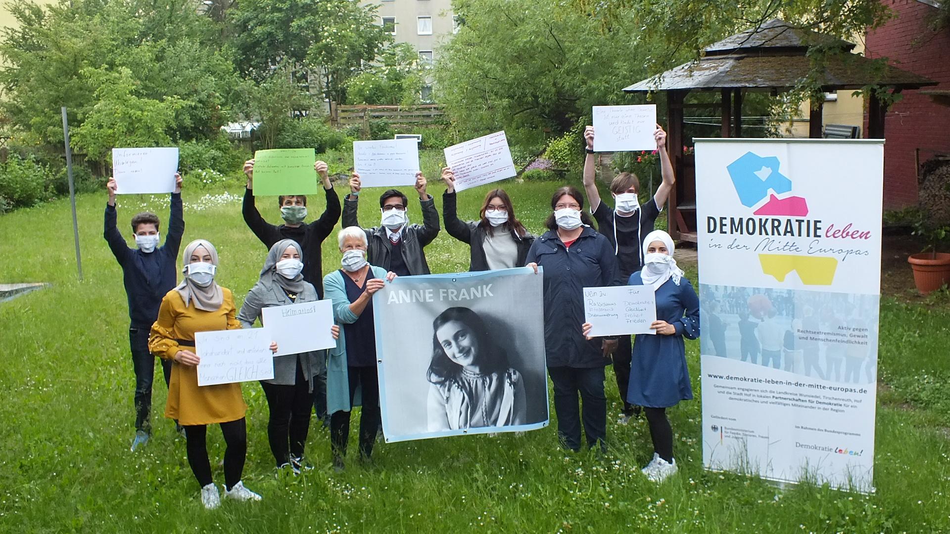 Das Bild zeigt die Peer Guides und die beiden Organisatorinnen mit einem Foto von Anne Frank (Foto: Stefan Denzler)